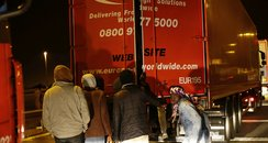 Migrants try to board a lorry
